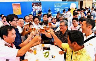 オリオンビールの創立60周年を記念したスペシャルイベントで、ビールを片手に盛り上がる来場者=11日午後、那覇市久茂地・タイムスビル1階エントランス