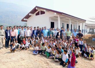 完成した幼稚園校舎に笑顔で「通いたい」と手を上げる子どもたちと関係者=7日、ラオス・アタプー県サナムサイ郡ターセンチャン村