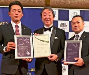 品評会の土屋守実行委員長(中央)から表彰される伊江島物産センターの知念寿人常務(左)=8日、東京都内のホテル