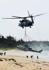 不時着した米軍UH1Yヘリをつり上げ移送するCH53ヘリ=8日午前10時16分、うるま市・伊計島(渡辺奈々撮影)