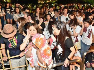 会場から漏れる音に必死に耳を傾ける安室奈美恵さんのファン=15日午後7時25分、宜野湾海浜公園