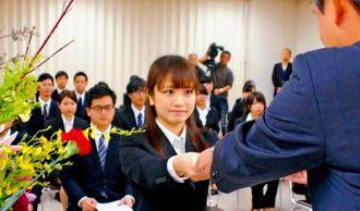 金城棟啓頭取(右)から採用辞令を受け取る新入行員=1日、琉球銀行本店