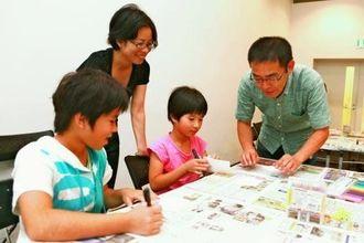 真喜屋さん(右)からアドバイスを受け、アニメーションのアイデアを練る子どもたち=7日、県立博物館・美術館
