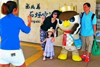 石垣市のマスコットぱいーぐると記念写真を撮る台湾からの観光客=南ぬ島石垣空港国際線ターミナル