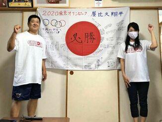 関係者が寄せ書きした日の丸を飾り、屋比久翔平を応援した父保さん(左)と母直美さん=2日、宜野湾市内(提供)