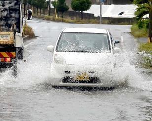 冠水した道路を水しぶきを上げて走る車=4日午後4時半すぎ、宮古島市平良西里(金城健太撮影)
