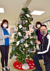 寄贈されたマスクを飾った特製のクリスマスツリーをPRする職員ら=14日、嘉手納町社会福祉協議会
