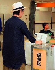 参院選の期日前投票所で1票を投じる有権者=23日午後、那覇市泉崎・那覇市役所