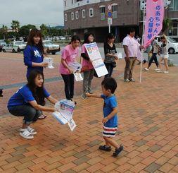 「のあちゃんを救う会」の街頭での呼び掛けに応じ募金する子ども=26日、北谷町美浜