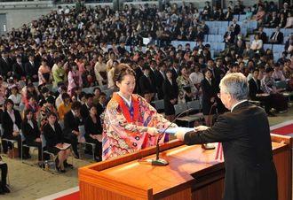 大城肇学長(右)から卒業証書を受け取る卒業生=19日午前、宜野湾市・沖縄コンベンションセンター