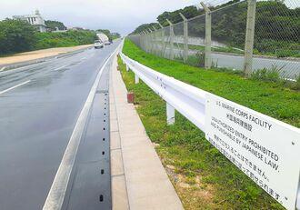 「無断で立ち入ることはできません。違反者は日本の法律に従って罰せられます」と書かれた基地側のガードレール=6月28日、宜野湾市・米軍普天間飛行場沿いの市道11号