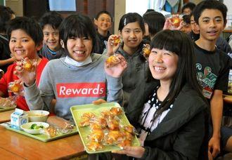 給食のデザートに出たマドレーヌを手に笑顔を浮かべる児童=南風原小学校