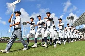 開会式で入場行進する高校球児たち=9日午前、コザしんきんスタジアム