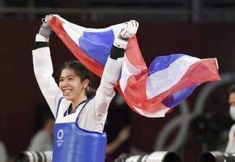 女子49キロ級で優勝し、国旗を手に笑顔を見せるタイのパニパック=幕張メッセ
