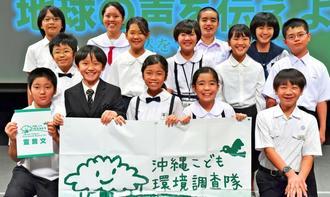 シンポジウム「地球の声を伝えよう」を終え、笑顔で記念写真に納まる沖縄こども環境調査隊メンバー=1日、那覇市・タイムスホール