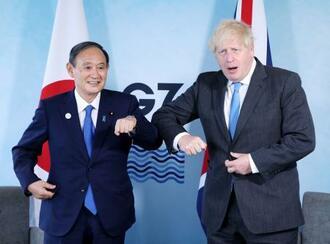会談を終え、肘でタッチを交わす菅首相(左)とジョンソン英首相=11日、英コーンウォール(代表撮影・共同)