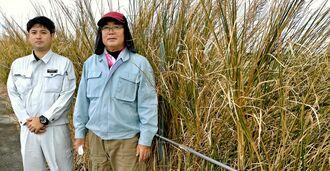 畑の周囲に植えたベチバーを紹介するパッションフルーツ農家の金城さん(右)=2020年12月22日、糸満市
