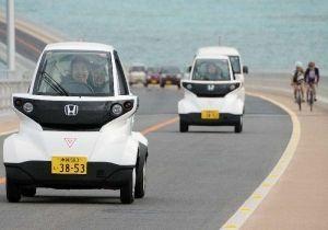 伊良部大橋を超小型電気自動車で渡る試乗会の参加者ら=伊良部大橋