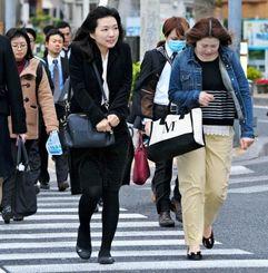 吹き付ける冷たい北風に身を縮める歩行者=9日午前8時すぎ、那覇市泉崎