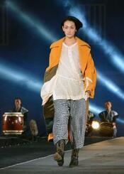 国産生地を使った衣装のファッションショーでさっそうと歩くモデルの冨永愛さん=7日夜、岡山市