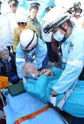 県警機動隊ともみ合い、道路に倒されて救急で搬送される女性=15日午前8時12分、米軍キャンプ・シュワブゲート前