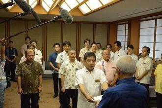 浦崎副知事(手前)から、新設された辺野古新基地問題対策課への辞令交付を受ける職員ら=1日午前、県庁