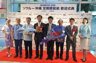 定期便の就航を喜ぶ大韓航空の金正洙氏(左から4人目)ら=5日、那覇空港国際線ターミナル到着ロビー