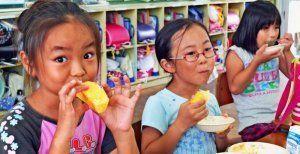 おいしそうに本部町産パインを頬張る児童たち=15日、伊豆味小中学校