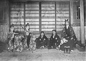 1925年に組踊の演目「二童敵討」の出演者を写した写真。場所は、明治政府による「廃琉置県」で首里城を追われた王家が移り住んだ中城御殿の軒先。昭和天皇の弟、秩父宮が来沖した際に披露された。右端には沖縄戦で亡くなるまで琉球古典芸能を守り育てた舞踊家、玉城盛重が写っている=同年5月、首里市(現・那覇市)、朝日新聞社所蔵