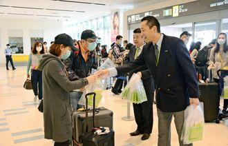 台北から到着した旅行客を笑顔で歓迎するソラシドエアの峯尾隆史副社長(中央右)=25日、那覇空港