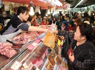 正月料理の食材を買い求める客でにぎわう公設市場=30日午前、那覇市松尾