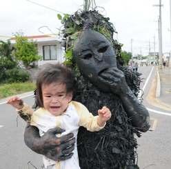 パーントゥに抱きかかえられて泣く赤ちゃん=25日、宮古島市平良島尻
