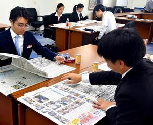 真剣な表情で紙面を読む受講者ら=24日、浦添市のオリオンビール本社