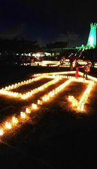 恒久平和を願いキャンドルでかたどられた「命」=22日午後8時すぎ、糸満市摩文仁・平和祈念公園