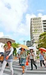 強い日ざしの下、日傘を差して歩く人たち=22日午後、那覇市泉崎・那覇市役所前