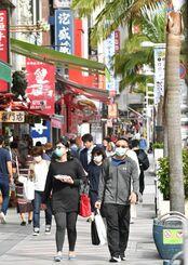 国際通りを歩くマスク姿の外国人観光客=14日午後、那覇市久茂地