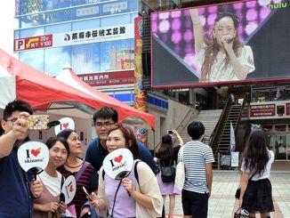 記念うちわを手に、大型モニターに映し出される安室奈美恵さんと記念撮影する来場者=15日、那覇市・てんぶす那覇前広場