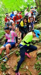 山中の滑りやすい急斜面をゆっくりと下りるトレイルランの参加者=10日、国頭村(下地広也撮影)