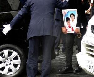 松永真菜さんと長女莉子ちゃんの告別式を終え、遺影を抱え車に乗り込む遺族=24日午前、東京都豊島区