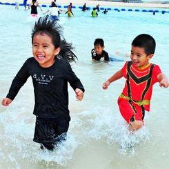 海開き宣言後、波打ち際で遊ぶ子どもたち=南城市・あざまサンサンビーチ