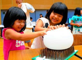 たくさんのくぎに風船を押しつける子どもたち=5日、沖縄市・県立総合教育センター
