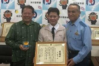 瑞慶山力署長(右)から感謝状が贈られたタクシー運転手の元俊晶さん(中央)=6月26日、浦添署