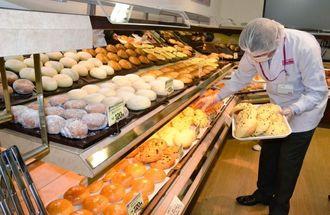焼きたてパンを陳列するマックスベーカリーの従業員=石垣市真栄里「マックスバリュやいま店」