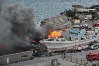 廃船が炎上し、黒煙が上がる火事現場=17日午後3時16分、那覇市・泊漁港