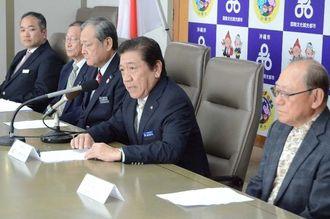 日本代表合宿の開催を発表する桑江朝千夫沖縄市長(右から2人目)ら関係者=沖縄市役所