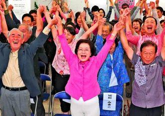当確の報を受け、支持者と万歳で喜ぶ城間幹子氏(中央)=16日午後8時5分、那覇市久茂地の選挙事務所