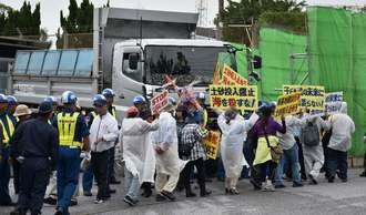 ゲートを出る工事車両に、プラカードを掲げて抗議する市民ら=23日、名護市の米軍キャンプ・シュワブゲート前