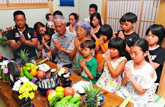 ウークイで集まり、手を合わせ先祖を見送る3世代の家族=17日夜、那覇市古島(喜屋武綾菜撮影)