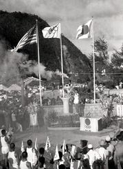 はちきれるばかりに打ち振られる日の丸に迎えられ、嘉陽に着いた聖火=1964年9月8日、久志村(現・名護市)嘉陽