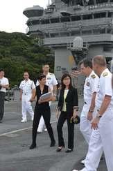 米海軍幹部らから空母ロナルド・レーガンについて説明を受ける稲田防衛相(右から3人目)=23日、神奈川県・米海軍横須賀基地